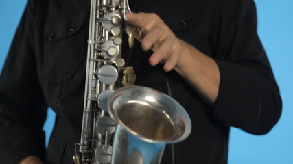 Close up of saxophone and  musician playing it