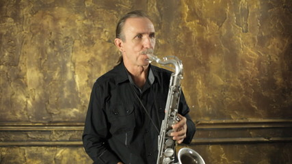 Saxophonist in black shirt playing the saxophone on a background
