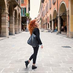 Redhead woman portrait walking in the street.