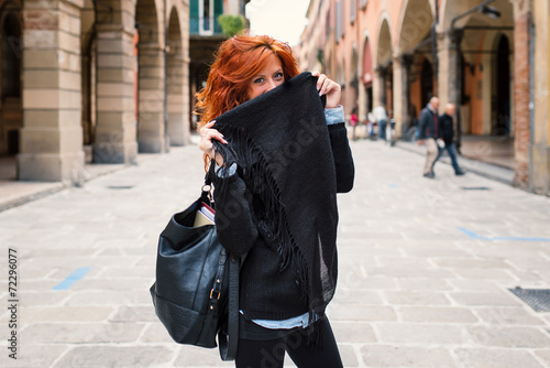 Happy redhead woman portrait hiding face in the street.