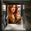 Young redhead student looking for book from shelf in college lib