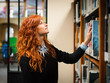 Young female student consulting book from shelf in public librar