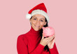 Smiling woman with christmas hat and a piggy-bank