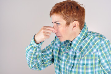 Woman holding her nose with her fingers because of  bad smell