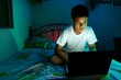 Young Teen in front of a laptop computer and on a bed