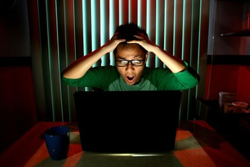 Young Teen acting surprised in front of a laptop computer