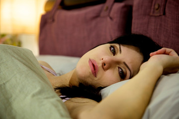 Sad woman in bed thinking