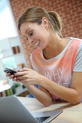 Smiling girl at home sending text message with smartphone