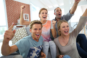 Roommates in apartment watching football game
