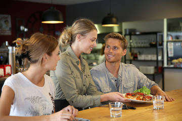 Young waitress serving students in restaurant