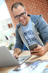 Guy with eyeglasses using smartphone at home