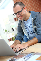 Cheerful guy at home using laptop computer