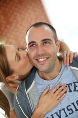 Girl kissing boyfriend on cheek