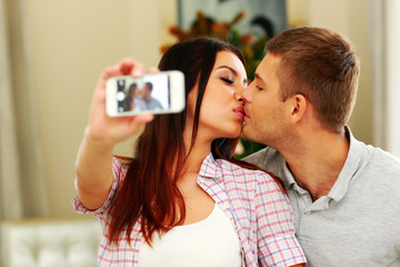 Young couple kissing and making selfie photo on smarphone