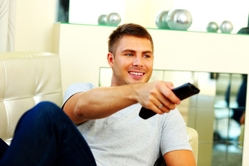 Smiling man on the couch watching TV at home