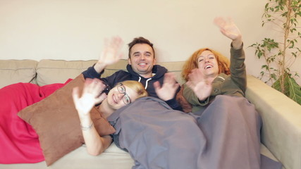 Group of ecstatic friends waving and relaxing on the sofa at hom