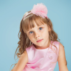 Little girl posing in a studio over colour background