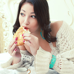 Perfect wake up concept. Young woman eating croissant