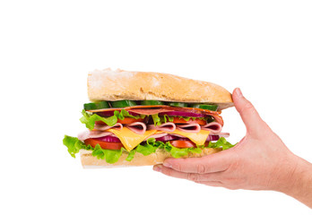 Sandwich with bacon and vegetables in hand.