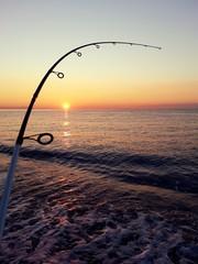 Canna da pesca piegata dalla forza di un pesce all'alba