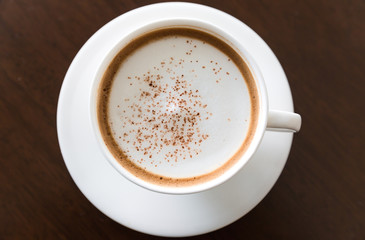 cup of fresh cappuccino on table