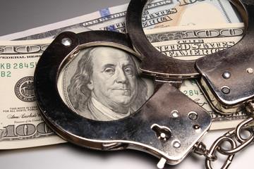 Handcuffs on money, criminal