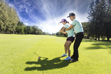 Young female golf player at Driving Range with a Golf Pro