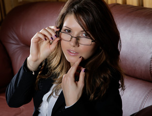 The girl in glasses and  business suit on a leather sofa