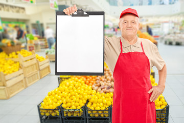 Market vendor holding clipboard in a supermarket
