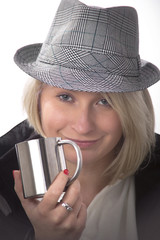 Young woman with a hat and a metallic cup