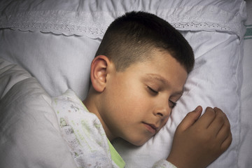 Cute boy asleep on white cushion