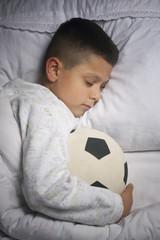 Cute boy asleep with football