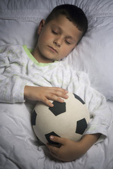Cute boy asleep with football
