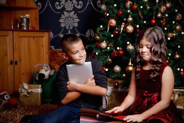 Cute little children opening a Christmas present