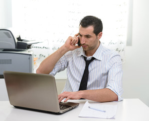 Businessman with laptop talking on the phone