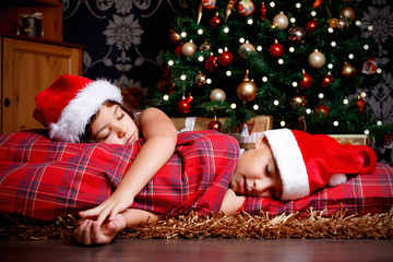 Sweet little siblings asleep while waiting for the gifts