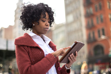 African American black woman in city using tablet pc