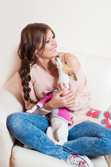 Beautiful woman sitting on an arm chair with a puppy