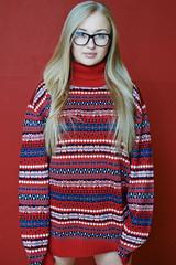 Девушка в свитере на красном фоне