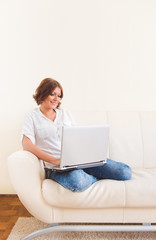 Woman using laptop on the sofa