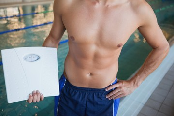 Mid section of a shirtless fit swimmer with weighing scales