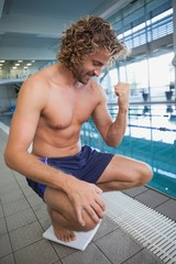 Fit shirtless swimmer happy with his weight by pool