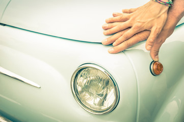Couple in love holding hands on a vintage classic car body