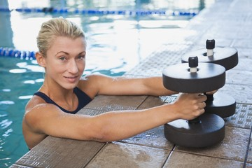 Female swimmer with foam dumbbells in swimming pool