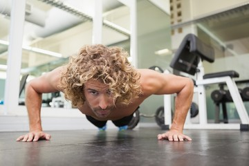 Handsome young an doing push ups in gym
