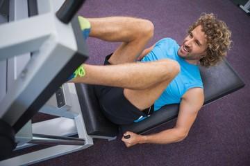 Handsome man doing leg presses in gym
