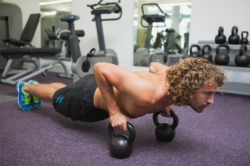 Man doing push ups with kettle bells in gym