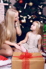 emotional girl with her mom posing beside a Christmas tree