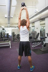Rear view of man lifting kettle bell in gym