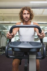 Man working out on exercise bike at gym